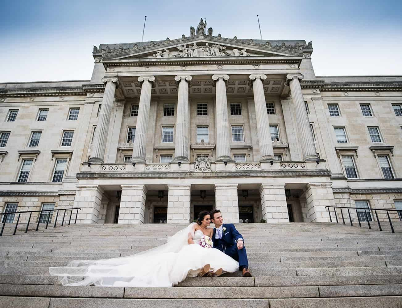 A couple pictured on the front steps at their wedding reception in Parliament Buildings