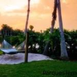 Disfruta después de un día ajetreado: Relájate en una hamaca en las verdes orillas del bello Lago Dorado. Una hamaca colgada sobre un pequeño cajón de arena en el lago al atardecer