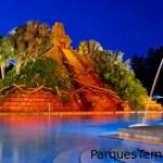 """La piscina Dig Site tiene una pirámide maya con un tobogán de agua en forma de """"jaguar que escupe agua"""" de 123 pies de largo, una fuente con chorro, un jacuzzi gigante para 22 personas, un bar de piscina, un área de recreación y una sala con videojuegos. The Mayan pyramid and spouting fountain at the Dig Site pool area, iluminada por la noche"""