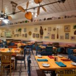Un ambiente alegre y con mucha luz domina este destino favorito de socios de Disney Vacation Club, en el que los ventiladores de ratán se balancean en el techo y coloridos servicios de mesa contrastan con las paredes pastel cubiertas con artefactos de navegación de época y chucherías isleñas. Mesas y reservados en Olivia's Café, con ventiladores de ratán que giran en el techo