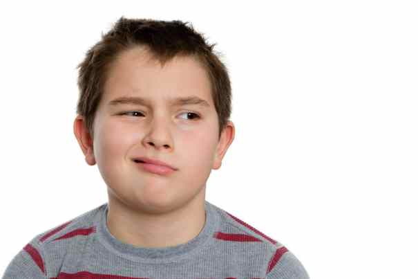 Close up Ten Year Old Boy Looking to the Right with Bored Facial Expression, Isolated on White Background.