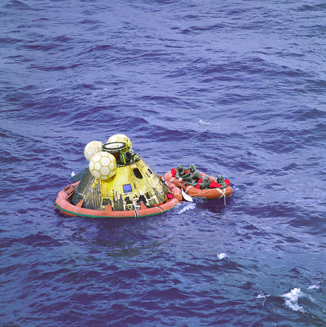 "(July 24, 1969) The Apollo 11 crew await pickup by a helicopter from the USS Hornet, prime recovery ship for the historic Apollo 11 lunar landing mission. The fourth man in the life raft is a United States Navy underwater demolition team swimmer. All four men are wearing Biological Isolation Garments (BIG). The Apollo 11 Command Module ""Columbia,"" with astronauts Neil A. Armstrong, Michael Collins, and Edwin E. Aldrin Jr. splashed down at 11:49 a.m. (CDT), July 24, 1969, about 812 nautical miles southwest of Hawaii and only 12 nautical miles from the USS Hornet."