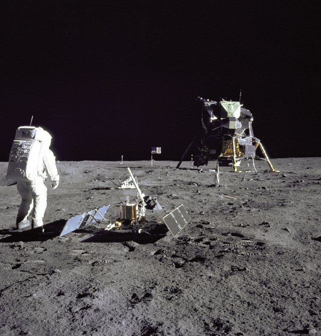 "Astronaut Edwin E.""Buzz"" Aldrin Jr., Lunar Module pilot, is photographed during the Apollo 11 extravehicular activity on the Moon. He has just deployed the Early Apollo Scientific Experiments Package (EASEP). In the foreground is the Passive Seismic Experiment Package (PSEP); beyond it is the Laser Ranging Retro-Reflector (LR-3); in the center background is the United States flag; in the left background is the black and white lunar surface television camera; in the far right background is the Lunar Module ""Eagle"". Astronaut Neil A. Armstrong, commander, took this photograph with a 70mm lunar surface camera."