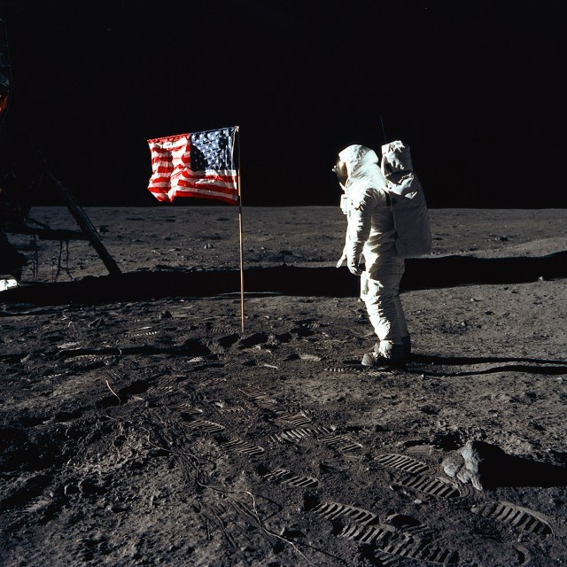 "(July 20, 1969) Astronaut Buzz Aldrin, lunar module pilot of the first lunar landing mission, poses for a photograph beside the deployed United States flag during an Apollo 11 Extravehicular Activity (EVA) on the lunar surface. The Lunar Module (LM) is on the left, and the footprints of the astronauts are clearly visible in the soil of the Moon. Astronaut Neil A. Armstrong, commander, took this picture with a 70mm Hasselblad lunar surface camera. While astronauts Armstrong and Aldrin descended in the LM, the ""Eagle"", to explore the Sea of Tranquility region of the Moon, astronaut Michael Collins, command module pilot, remained with the Command and Service Modules (CSM) ""Columbia"" in lunar-orbit."