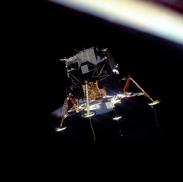 "The Apollo 11 Lunar Module (LM) ""Eagle"", in a landing configuration is photographed in lunar orbit from the Command and Service Modules (CSM) ""Columbia"". Inside the LM were Commander, Neil A. Armstrong, and Lunar Module Pilot Edwin E. ""Buzz"" Aldrin Jr. The long ""rod-like"" protrusions under the landing pods are lunar surface sensing probes. Upon contact with the lunar surface, the probes send a signal to the crew to shut down the descent engine."