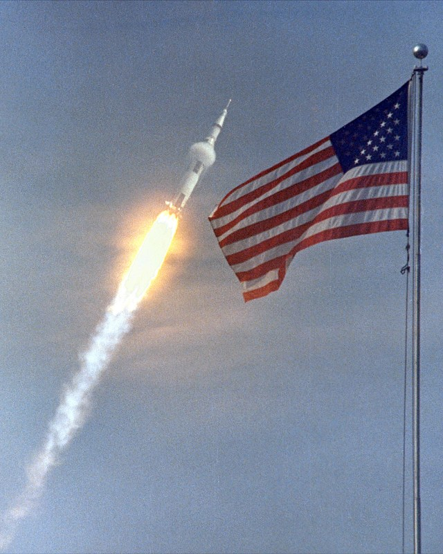 The American flag heralds the flight of Apollo 11, the first Lunar landing mission. The Apollo 11 Saturn V space vehicle lifted off with astronauts Neil A. Armstrong, Michael Collins and Edwin E. Aldrin, Jr., at 9:32 a.m. EDT on July 16, 1969, from Kennedy Space Center's Launch Complex 39A. During the planned eight-day mission, Armstrong and Aldrin will descend in a lunar module to the Moon's surface while Collins orbits overhead in the Command Module. The two astronauts are to spend 22 hours on the Moon, including two and one-half hours outside the lunar module. They will gather samples of lunar material and will deploy scientific experiments which will transmit data about the lunar environment. They will rejoin Collins in the Command Module for the return trip to Earth.