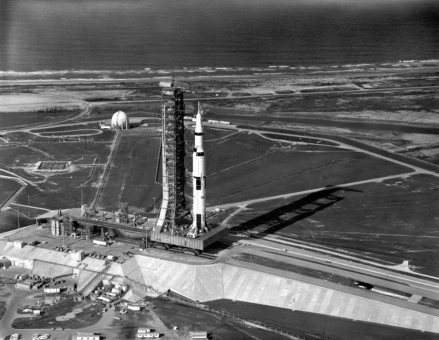 The Transporter nears the top of the five percent incline at Launch Complex 39A with the Apollo 11 Saturn V.