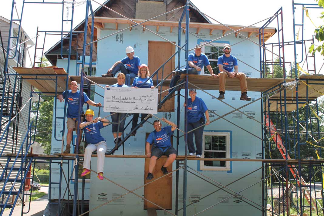 Spencer savings bank donates money and volunteer labor to for Help building a house