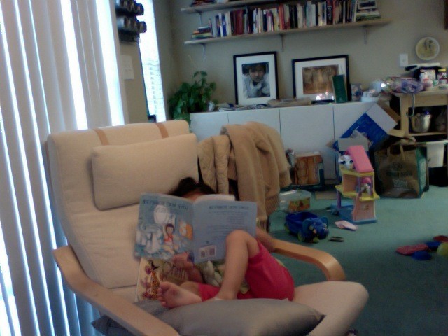 "i love it when roenne ""reads"" by herself. she's been lounging in that chair and reading for 20 min now. =)"