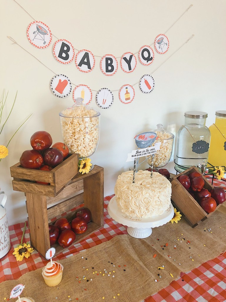 "Fire up the grill, mow the back yard, put out some decorations, and throw that apron on (Bonus points if it says ""Kiss the Cook""). It's time for a BBQ! and by that, I mean a bbq themed baby shower. Whether you're serving hot dogs or burgers and beer, this post has you covered. After you are finished reading you'll be able to host the perfect baby BBQ themed baby shower - no venue rental required."
