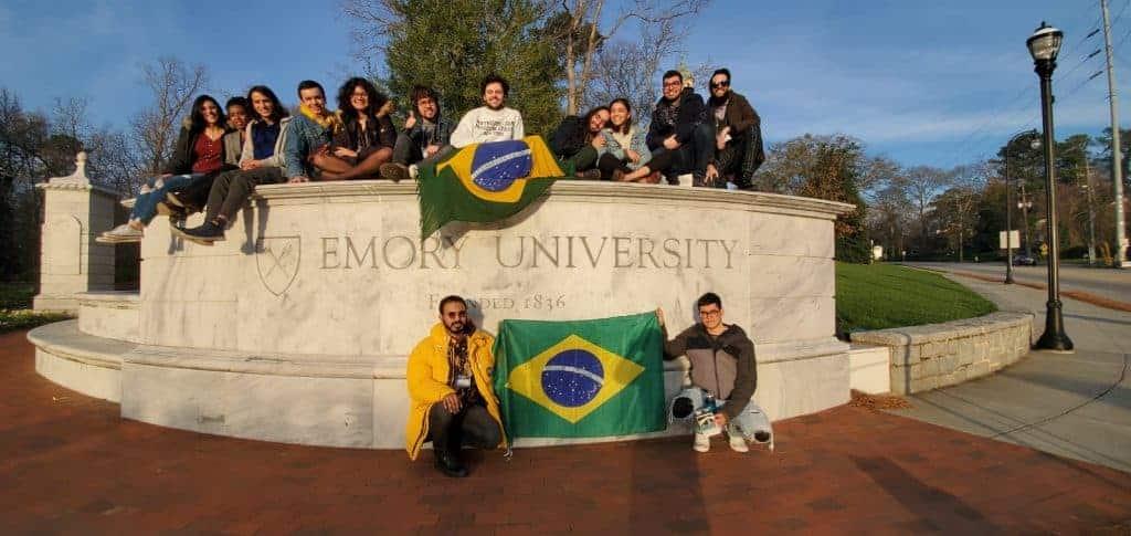 FLTAs Brasileiros sentados em um letreiro da Emory University nos EUA segurando uma bandeira dos Brasil