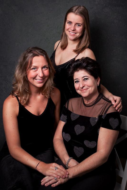 Drie vrouwen; moeder met twee dochters, gefotografeerd als portret, stijlvol en klassiek.