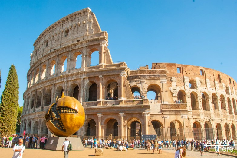 Full view of Colosseum in Rome, Italy, with statue of pomegranate in front