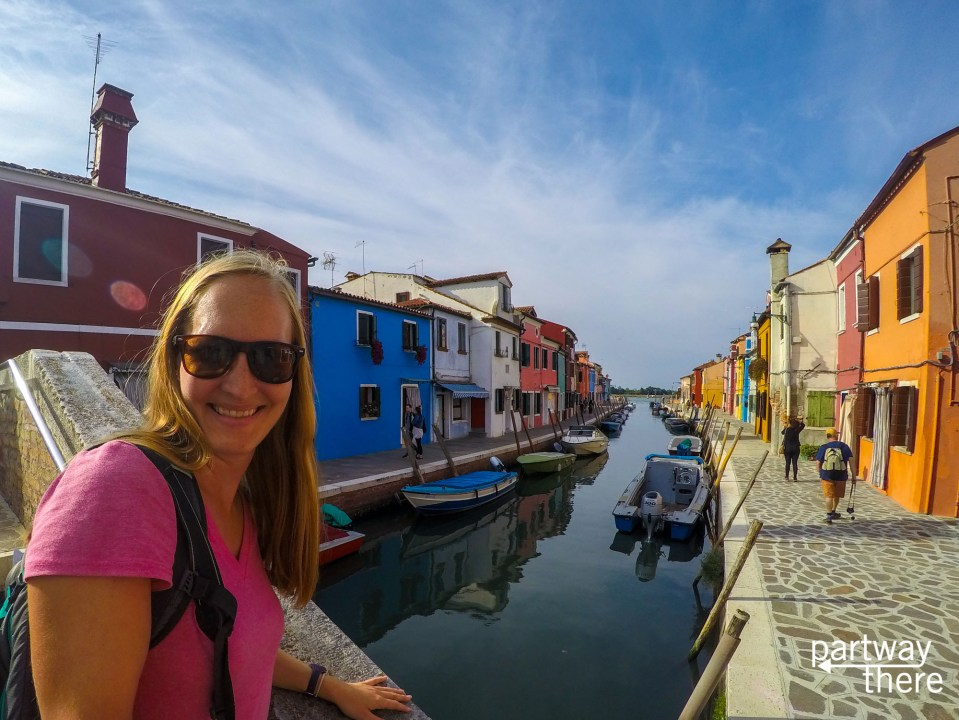 Amanda Plewes in front of colorful houses along a canal in Burano, Italy