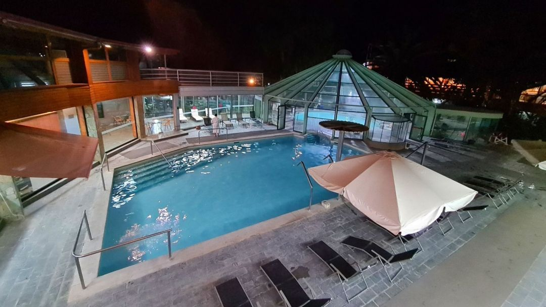 vista de una de las piscinas exteriores e interior al anochecer