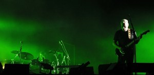 David Gilmoure in Munichj in 2006 on a concert stage with green light and smoke, alone, withh pices of the drupset visible opposite to him