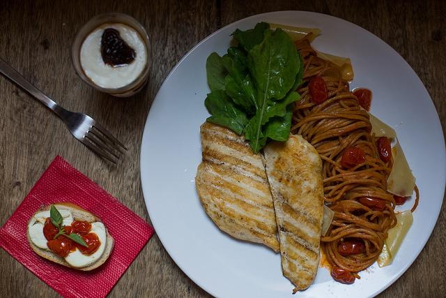 Frango grelhado com espaguete integral ao molho de tomate, rúcula fresca, tomatinhos confitados e lascas de parmesão