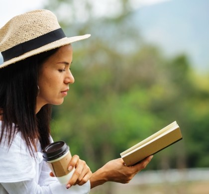 asian women read books and drink coffee in the park.