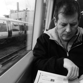 Turning a page   Last train (and last train pic) until Monday. by southcoasting batterseapowerstation, blackandwhite, black_and_white, newspaperreader, passengers, traingame,