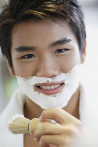 homme utilisant un blaireau pour préparer sa peau au rasage