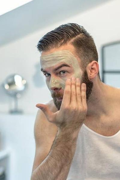 homme nettoyant son visage pour éliminer les points noirs