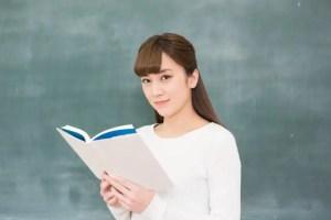 黒板の前に立つ女子大生