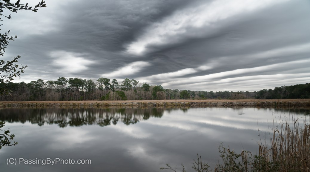 Striped clouds over pond
