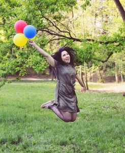 woman jumping while holding four balloons