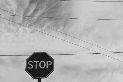 grayscale photography of stop signage under sky