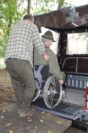 guide assisting hunter in wheelchair