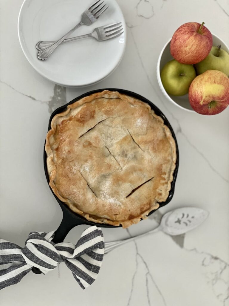 Cast Iron Skillet Apple Pie Finished with Plates and Apples