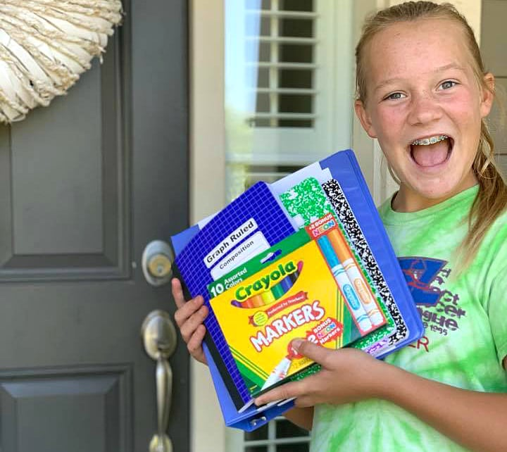 girl holding school supplies