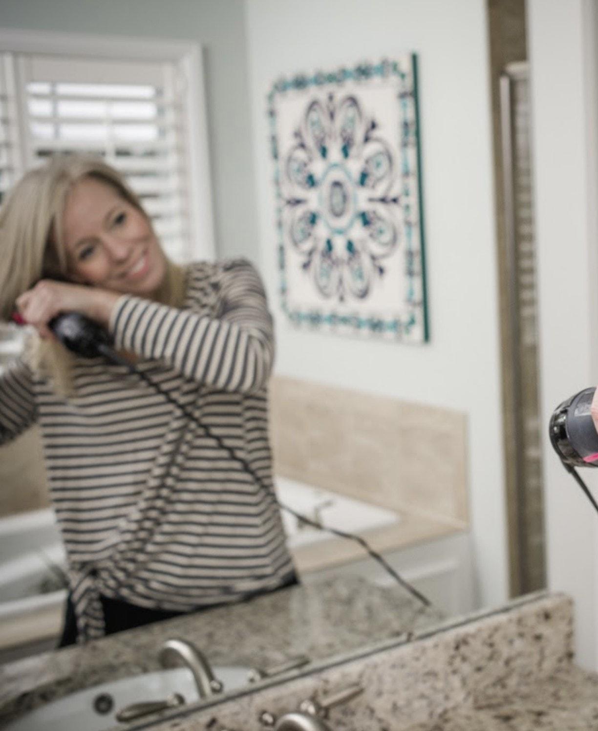fixing hair in mirror
