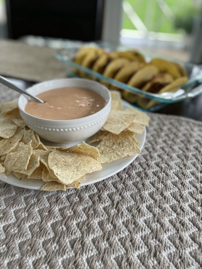 cheese dip with tacos in the background