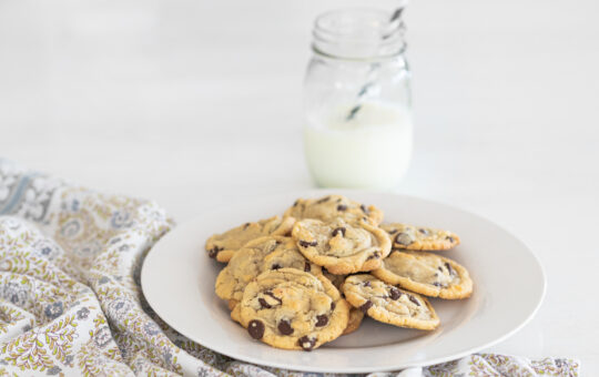 Chocolate chip cookies on a plate with a glass of milk with a straw