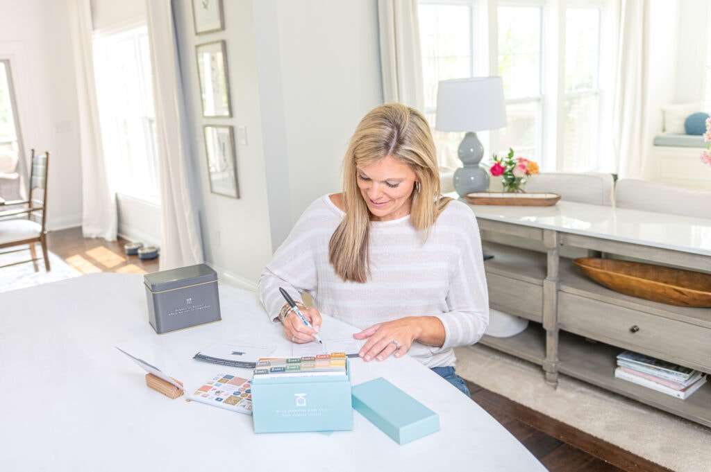 Ashley making grocery list with low calorie menu set and gray tin