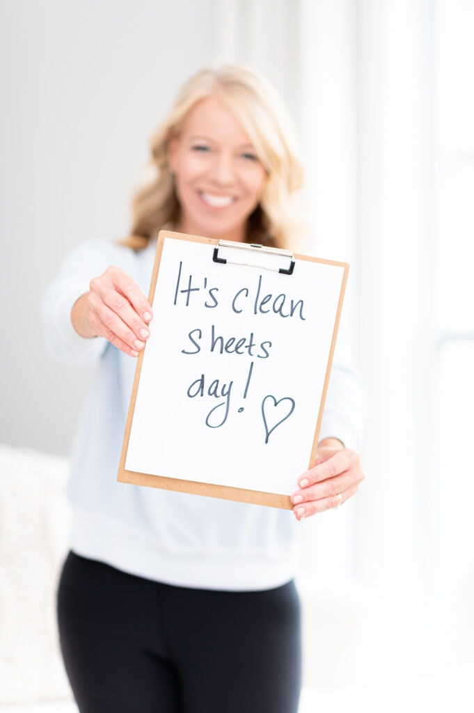 """Laurie holding a sign that says, """"it's clean sheets day"""""""