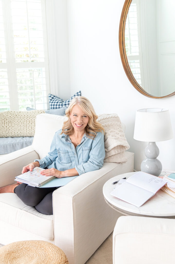 Laurie sitting in chair with blue planner