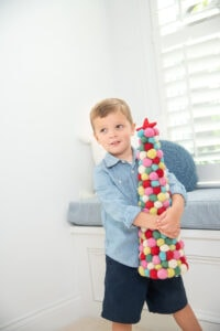 Little boy holding colorful Christmas tree
