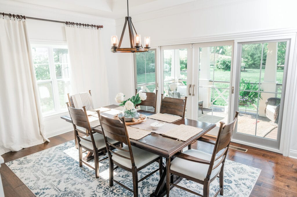Breakfast room with dark table and chairs and light curtains and walls