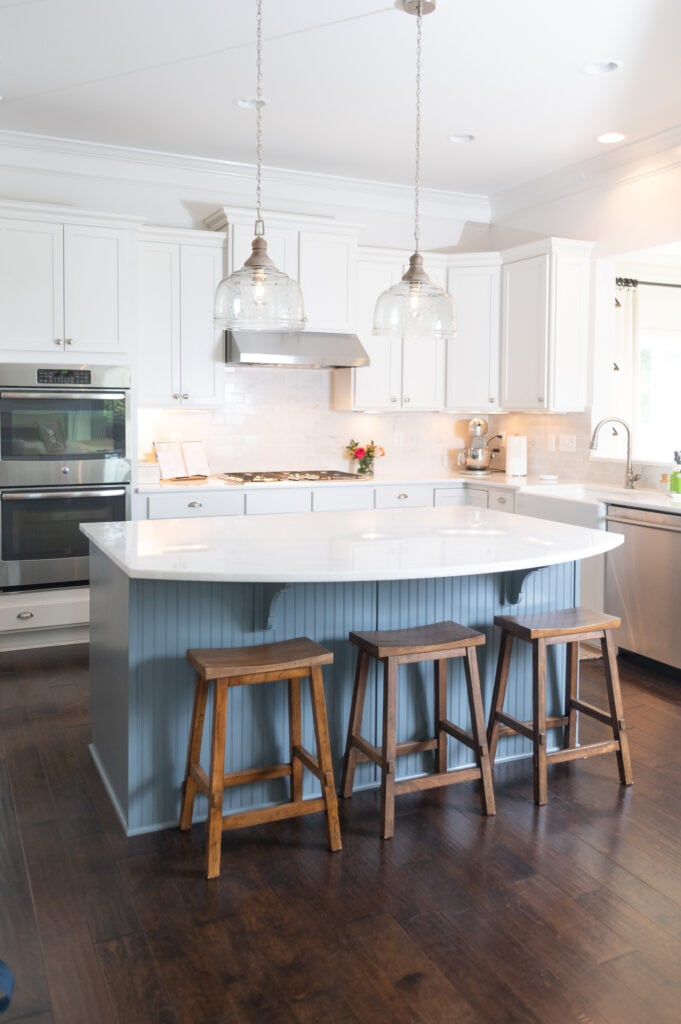 White kitchen with three wooden bar stools