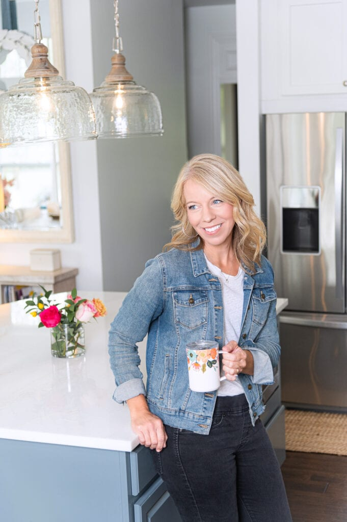 Laurie leaning on kitchen counter with rifle coffee mug