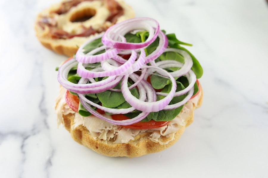 Adding veggies to party sandwiches
