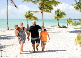 Justin Zackham and his family walk along the beach with palm trees in the background