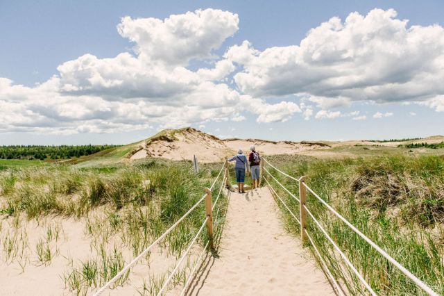 two hikers pause at the end of a sandy path on the dunes at central coast park in prince edward island.
