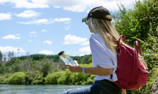 woman holding reusable plastic water bottle