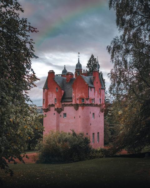pink castle with rainbow above
