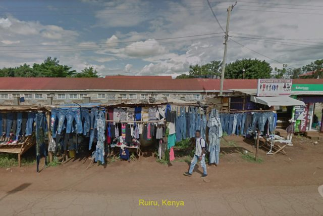 man strolling past jeans vendor