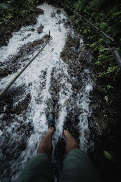 man's legs standing in waterfall