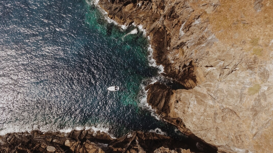 aerial view of boat leaving a sea cove